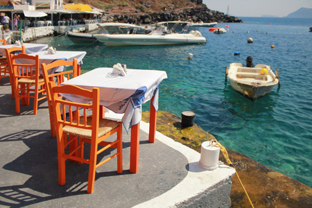 orange chairs: greek tavern with orange wooden chairs by the sea coast, Greece, Santorini island in Cyclades, selective focus