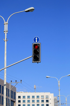 trafficlight: Red traffic lights with arrow against blue sky background