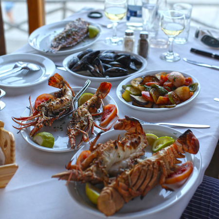 taverna: Lobster and vegetables an the table in typical greek taverna, Crete, Greece. Selective focus Stock Photo
