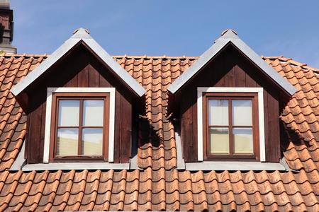 garret: orange tiled roof on blue sky and garret windows in old house, Vilnius