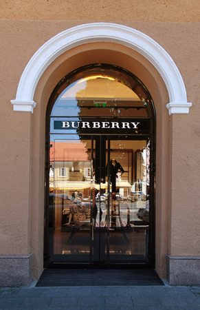 distributing: VILNIUS, LITHUANIA - JULY 19, 2015: The Burberry shop in Vilnius, Lithuania. Burberry is British luxury fashion house, distributing outerwear, fashion accessories, fragrances, sunglasses, and cosmetics.