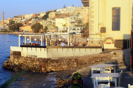 rethymno: RETHYMNO, GREECE - JULY 24, 2015: People in traditional greek tavern on the sea coast in the harbor of Rethymno, Crete, Greece. Sunset light.