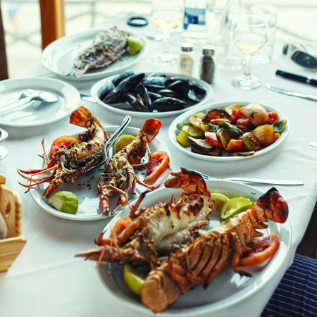 lobster dinner: Lobster and vegetables an the table in typical greek taverna, Crete, Greece.  Stock Photo
