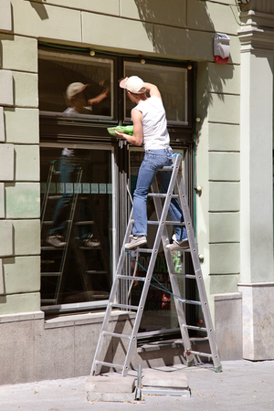 VILNIUS, LITHUANIA - JULY 19, 2015: Professional window cleaner working on a ladder, Vilnius, Lithuania