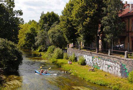 vilnius: VILNIUS, LITHUANIA - JULY 19, 2015: People and canoe boat in River Vilnele near Uzupis neighborhood, Vilnius, Lithuania. Editorial