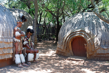 LESEDI VILLAGE, SOUTH AFRICA-JAN 1,2008: Zulu men wearing warrior dress near tribal straw house in Lesedi Cultural village, South Africa. Men in Zulu clan wear animal skin decorated multicolored beads.