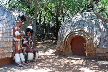 LESEDI VILLAGE, SUD AFRICA-Jan 1,2008: Zulu uomini indossano abito guerriero vicino a casa di paglia tribale nel villaggio di Lesedi Cultural, Sud Africa. Uomini in Zulu clan indossare pelle animale decorato perline multicolori.