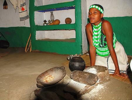 zulu: LESEDI CULTURAL VILLAGE,SOUTH AFRICA - JAN 1, 2008: Zulu woman in handmade dress cooking maize meal at tribal house at Lesedi Village, South Africa.Maize meal is basic Zulu ingredient.