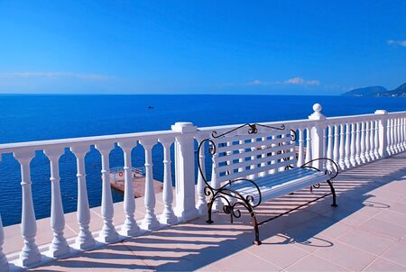 balustrade: Summer view with classic white balustrade, bench and empty terrace overlooking the sea Stock Photo