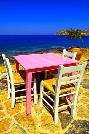 alfresco: Alfresco restaurant - traditional greek tavern with pink table and white chairs on the beach of Mediterranean sea,Crete, Greece. Selective focus