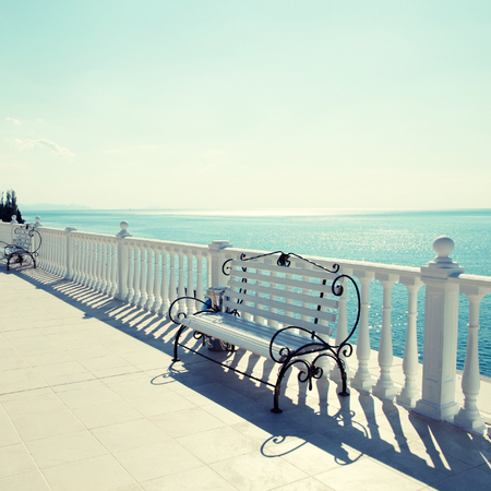 bannister: Summer view with classic white balustrade, benches and empty terrace overlooking the sea, sunlight. Square toned image, instagram effect