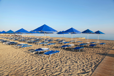 longue: Blue umbrellas and chaise longue on empty sandy beach in the morning, Crete, Greece