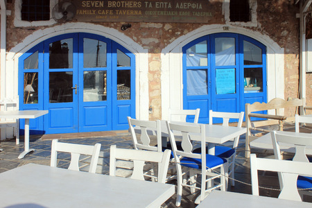 rethymno: RETHYMNO, GREECE - JULY 24, 2015: Outdoor restaurant with white and blue tables and chairs in the old Venetian port of Rethymno on Crete island in Greece
