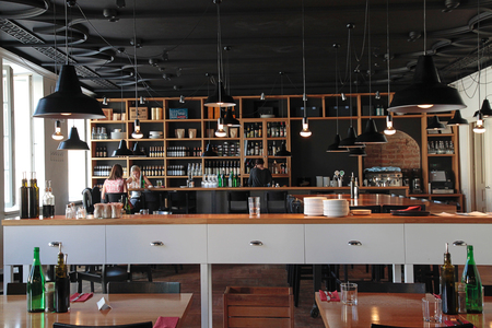 restaurant dining: VILNIUS, LITHUANIA - JULY 21, 2015: People in the modern cafe with cozy interior and with open kitchen, Vilnius, Lithuania. Editorial