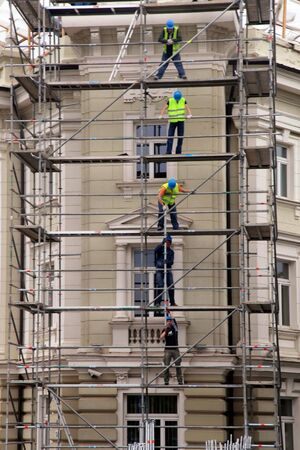 scaffolds: VILNIUS, LITHUANIA - JULY 20, 2015 : Team work at construction site, workers passing metal formworks on scaffolds, Vilnius, Lithuania. Editorial
