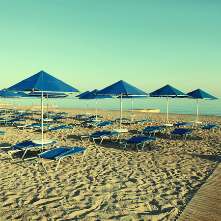 longue: Blue umbrellas and chaise longue on empty sandy beach in the morning, Crete, Greece. Square vintage toned image, instagram effect Stock Photo