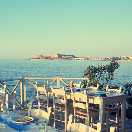 taverna: traditional greek outdoor restaurant on terrace with sea view at street village restaurant, Crete, Greece. Sunset light. Square toned image Stock Photo