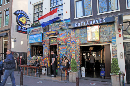 coffeeshop: AMSTERDAM, NETHERLANDS - MAY 5, 2016: Cityscape with people and the coffeeshop Bulldog in Amsterdam, Netherlands. Bulldog was the first coffeshop and laid the benchmark for the contemporary coffeeshop.