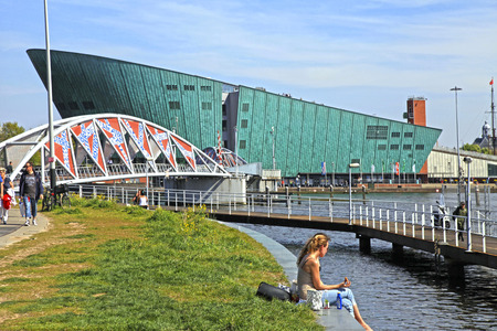 nemo: AMSTERDAM, NETHERLANDS - MAY 6, 2016: People on embankment near Science Center NEMO designed by Renzo Piano (1997) - science educational museum, knowledge institute and center of tourism in Amsterdam, Netherlands.