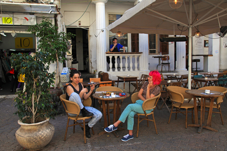 sidewalk talk: TEL AVIV, ISRAEL - APRIL 3, 2016:Israeli young women sitting in street outdoor cafe in Tel Aviv, Israel. Selective focus