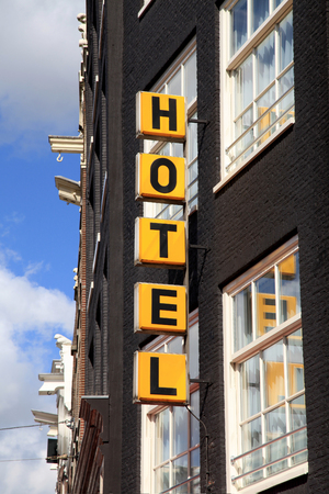 brick building: Vertical yellow Hotel sign over the entrance to the brick building in Amsterdam Stock Photo