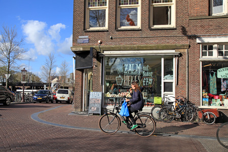 dutch girl: AMSTERDAM, NETHERLANDS - MAY 3, 2016: Local woman on bicycle in historical center in Amsterdam, the Netherlands. Bicycles outnumber the people in Amsterdam: 760,000 citizens and nearly a million bikes.