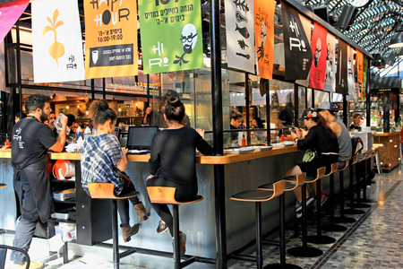 TEL AVIV, ISRAEL - APRIL 7, 2016: People having lunch in a modern open kitchen restaurant in the new Sarona food market, Tel Aviv, Israel