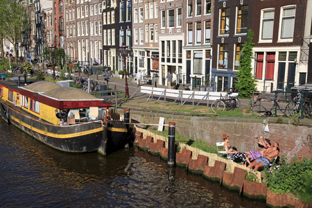 house float on water: AMSTERDAM, NETHERLANDS - MAY 8, 2016: People relax on canal embankment near houseboat in Amsterdam,Netherlands. Houseboats are high demand very popular and common form of housing in Amsterdam
