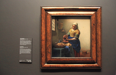 johannes: AMSTERDAM, THE NETHERLANDS - MAY 4, 2016: Oil Painting of The Milkmaid by Johannes Vermeer from 1660 in the famous Rijksmuseum in Amsterdam, The Netherlands Editorial