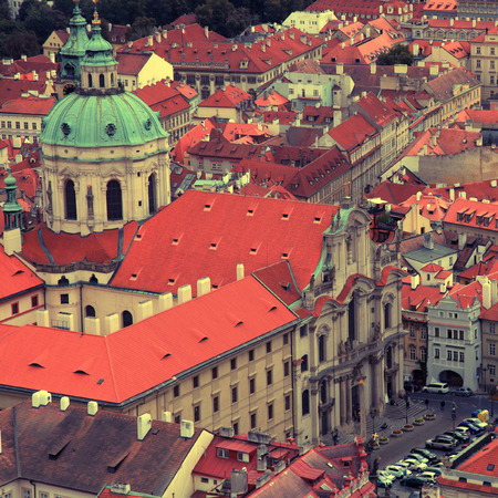 st nicholas: Panorama of Prague Old Town with red roofs and St. Nicholas Church in the quarter of Mala Strana, Czech Republic. square vintage toned image