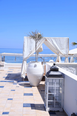 bawl: romantic terrace patio of seaside resort with outdoor furniture, flower bawl and sea view, Crete, Greece. Selective focus Stock Photo