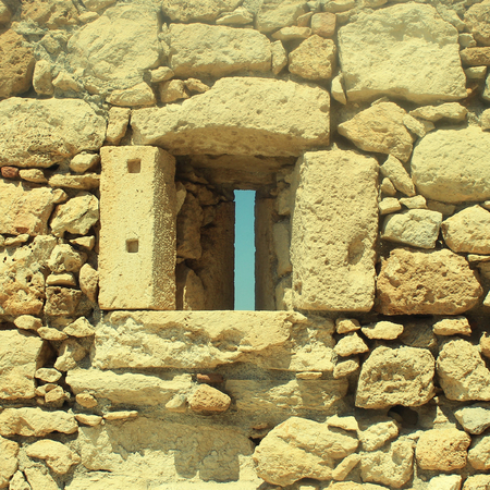 greece granite: Window in old stone wall ruins of a medieval fortress on Crete Island, Greece. Square toned image