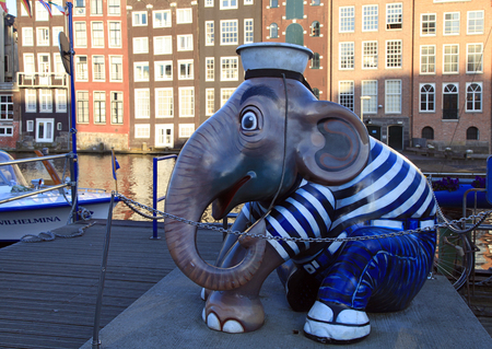 canal parade: AMSTERDAM, THE NETHERLANDS - MAY 03, 2016: Sculpture of elephant sailor at pier of canal on Damrak street in city center, Amsterdam, Netherlands. Selective focus Editorial