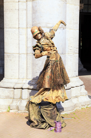 AMSTERDAM, NETHERLANDS - MAY 4, 2016: Street performer - golden painted mime artist in city center, Amsterdam, Netherlands. Living statues are the entertainment for the tourists.