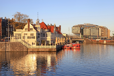 AMSTERDAM, NETHERLANDS - MAY 3, 2016: Starter point of canal cruise on Amstel river near Central Station, Amsterdam, Netherlands. Sunset light. Editorial