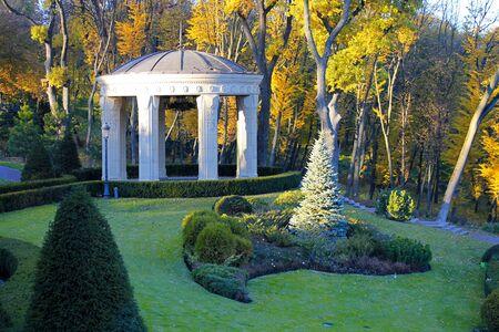 rotunda: White classic pavilion with columns in autumn park.