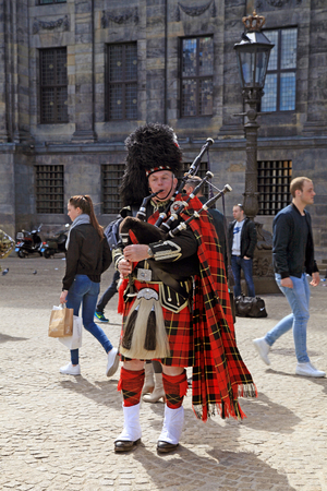 AMSTERDAM, NETHERLANDS -  MAY 3, 2016: Street musician with Scottish traditional bagpipes on the Dam Square, Amsterdam, Netherlands. Editorial