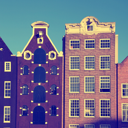 Traditional facade of brick dutch medieval buildings in Amsterdam, Netherlands. Square toned image. Stock Photo
