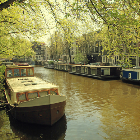 Beautiful Amsterdam scene with traditional dutch old buildings and houseboats in the canal, Jordaan neighborhood, Amsterdam, the Netherlands. Square vintage toned image