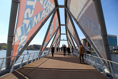 AMSTERDAM, NETHERLANDS - MAY 6, 2016: People walking on the modern bridge near the Nemo museum in Amsterdam, Netherlands Editorial