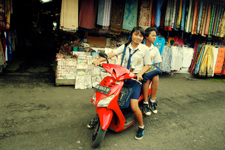 BALI, INDONESIA - JANUARY 4, 2011: Two indonesian schoolgirls with a motorbike near traditional asian street market in Bali, Indonesia. The use of motorbikes as transport for all family is commonplace in Bali. Editorial
