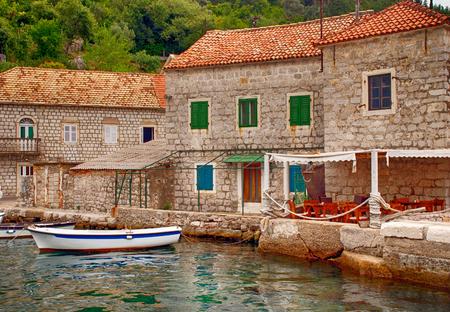 kotor: Old mediterranean stone houses and pier in Kotor bay, Montenegro Stock Photo