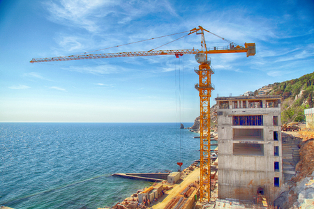 investment real state: Tall yellow crane on construction of the new expensive apartment building on the sea coast, Crimea