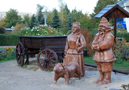 wood statue of ukrainian peasants and cart in the garden Stock Photo