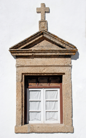 stucco: old small shabby window in white stone rural church, Portugal.