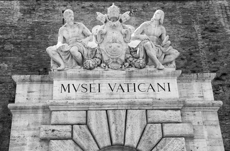 Main entrance to the Vatican Museum with sign and sculptures in Rome, Italy. Black and white image