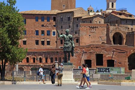 ROME, ITALY - JULY 17, 2017: Tourists and bronze statue of Emperor Trajan on Via dei Fori Imperiali near Roman Forum, Rome, Italy.