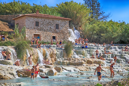 SATURNIA, ITALY - JULY 26, 2017: Natural spa with waterfalls and hot springs at Saturnia thermal baths, Grosseto, Tuscany, Italy. Tourists swimming and relaxing in hot springs at Cascate del Mulino in Saturnia Editorial