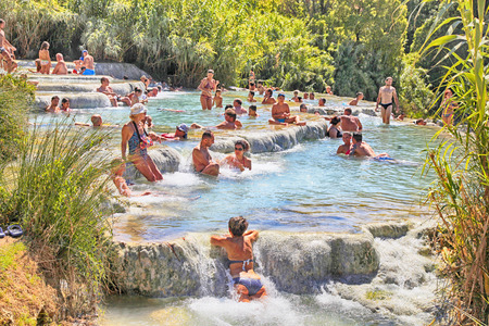 SATURNIA, ITALY - JULY 26, 2017: Tourists swimming and relaxing in hot springs at Cascate del Mulino in Saturnia, Grosseto, Tuscany, Italy. This world famous natural spa has natural waterfalls and hot