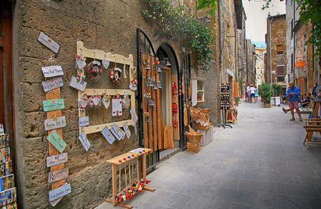 PITIGLIANO, ITALY - JULY 26, 2017: Narrow alley with gift shop in gorgeous etruscan and medieval town Pitigliano built of tuff stone, Tuscany, Italy. Called little Jerusalem for the historical presence of a Jewish community.